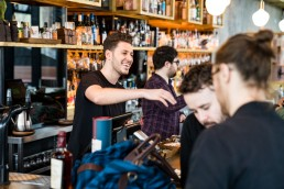 barman talks to customers at Aether