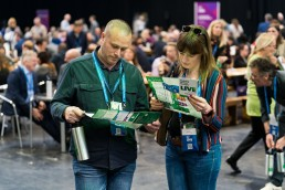 Large scale corporate event photography - Helping Britain Prosper Live delegates looking through their event schedules