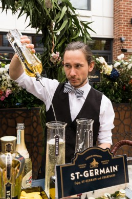 corporate brand giveaways - St Germain alcohol sampling - bar tender pours samples of St Germain Spritz