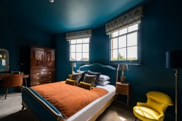 wide angle photo of a blue bedroom