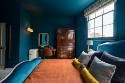 Blue bedroom with orange cover and blue pillows
