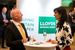 guests laughing with Lloyds branding behind them